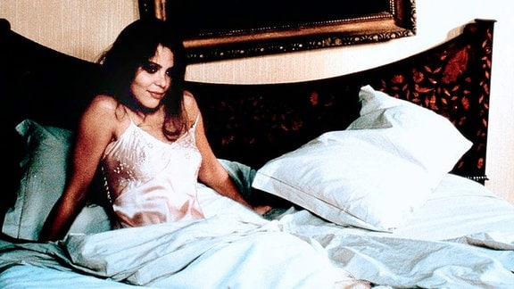 Eine attraktive junge Frau sitzt aufgestützt im Bett und schaut lächelnd nach vorne.