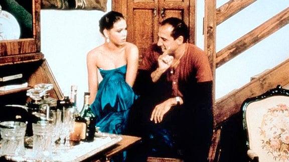 Eine Frau und ein Mann sitzen auf einer Treppe und unterhalten sich.