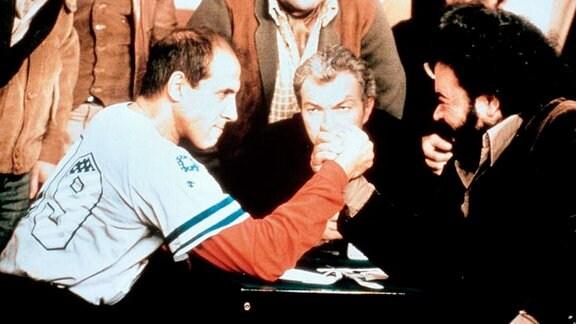 Zwei Männer machen Armdrücken, während andere Männer im Hintergrund ihnen dabei zusehen.