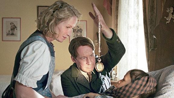 Vater Rudi (Ulrich Noethen, Mitte) und seine Frau Käthe (Fanny Stavjanik) beruhigen den kleinen Udo (Alexander Kalodikis), der von einem fanatischen Jungscharführer so sehr aufs Ohr geschlagen wurde, dass er einen Hörsturz erlitt.