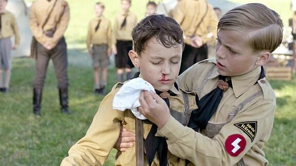 Der kleine Udo (Alexander Kalodikis, li.) ist bei einer Wehrübung von einem fanatischen Jungscharführer so sehr aufs Ohr geschlagen worden, dass er einen dauerhaften Schaden davontragen wird.