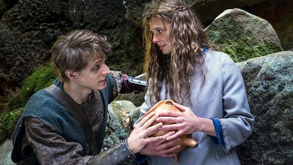 Szenenbild - Der süße Brei - Jolanthe (Svenja Jung) und Veit von Hammerlitz (Merlin Rose) stehen auf einer Waldlichtung dicht bei einander, umfassen den magischen Topf und blicken sich tief in die Augen.