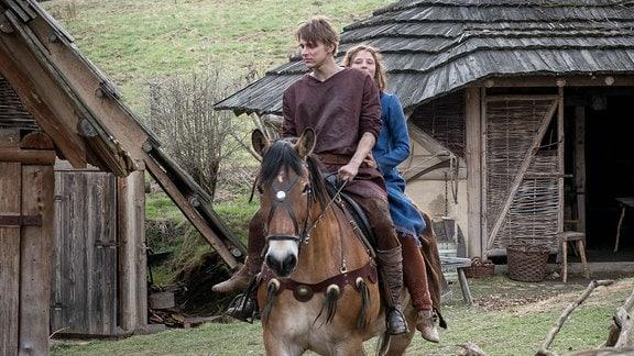 Jolanthe (Svenja Jung) und Veit von Hammerlitz (Merlin Rose) reiten auf einem Pferd in das Dorf.