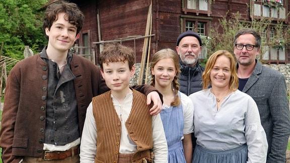Sechs Personen stehen zusammen vor einem alten Haus. Ein Jugendlicher, zwei Kinder und eine Frau tragen historische Kleidung. Die beiden Männer hinter ihnen tragen moderne Kleidung.