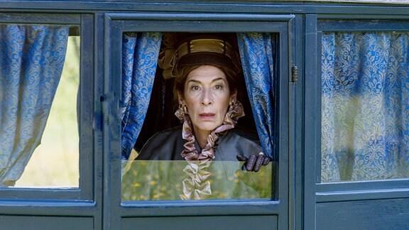 Eine Frau in einer Kutsche schaut überrascht aus dem Fenster.