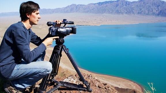 Ein junger Mann mit einer Stativkamera blickt von einer Erhöhungauf  eine Landschaft mit Gebirge und einem gorßen See.