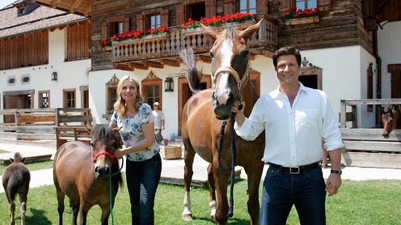 Susanne Michl und Francis Fulton Smith stehen gemeinsam mit einem Pferd und einem Pony vor einem Bauernhaus.