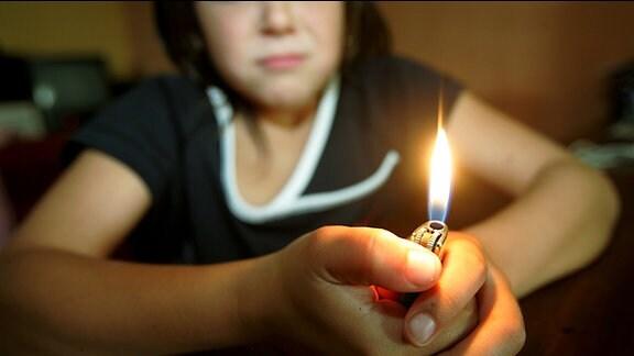 """Ein Kind """"spielt"""" mit Feuer"""