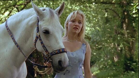 Eine Frau neben einem weißen Pferd