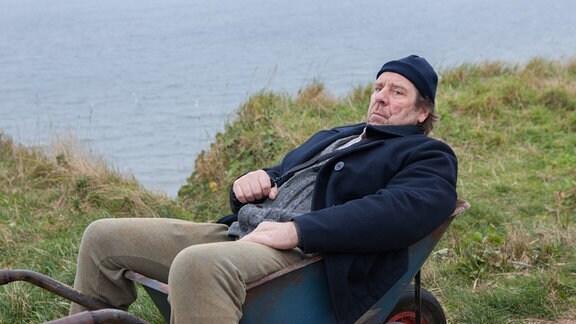 Ein Mann liegt mit grimmigem Blick in einer Schubkarre. Im Hintergrund eine grasbewachsene Düne und das Meer.