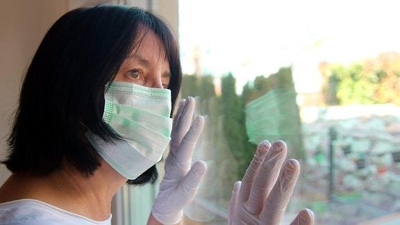 Eine Frau mit Mund-Nasen-Schutz sieht aus einem Fenster
