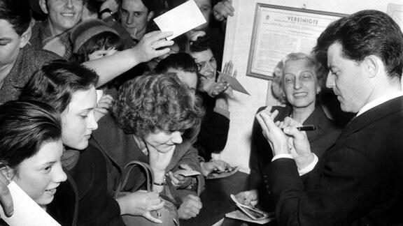 """Der französische Schauspieler Gérard Philipe erfüllt am Abend des 18.01.1957 nach einer Spätvorstellung seines Films """"Die Abenteuer des Till Ulenspiegel """" in einem Kino in Ostberlin Autogrammwünsche."""