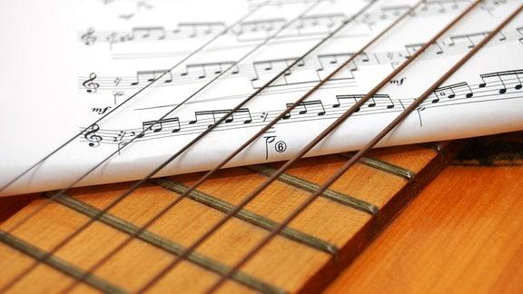 ein Notenblatt ist unter die Saiten einer Gitarre gelegt