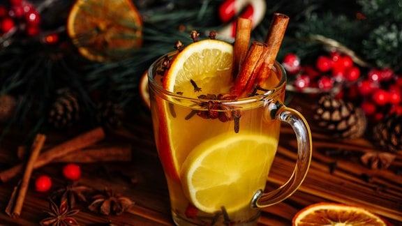 Ein Glas mit weißem Glühwein mit Weihnachtsdekoration darum
