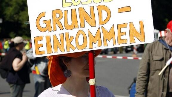 Eine Frau demonstriert für ein - Bedingungsloses Grundeinkommen -