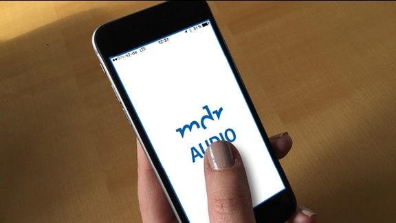 """Eine Hand hält ein Iphone. darauf steht """"MDR AUdio. Das inklusive Hörangebot"""""""