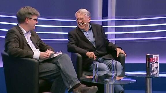 Zwei Männer sitzen auf der Bühne lachen sich an.