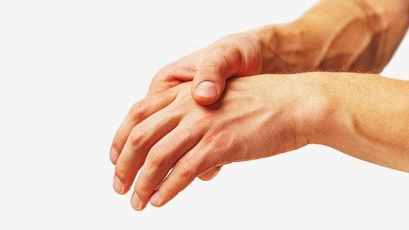 Aufnahme zweier Hände einer Person, wobei die rechte Hand die linke vorsichtig umfasst.