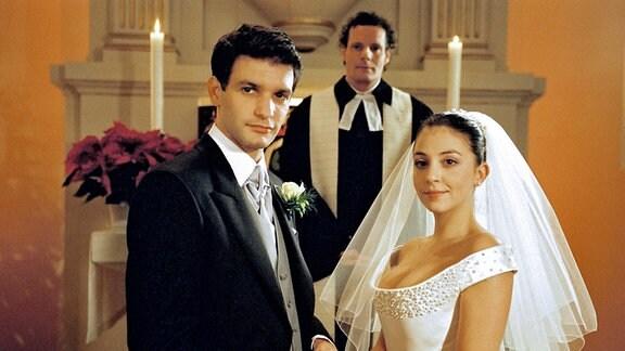 Thomas Berner (Luca Zamperoni), Pastor (Dirk Glodde) und Julia Weimann (Arzu Bazman) vor dem Traualtar