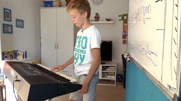 Junge spielt E-Piano