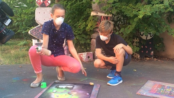 Zwei Kinder mit Spraydosen
