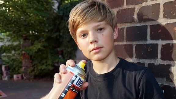 Junge hält Spraydose