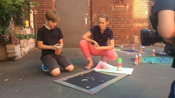 Ein Mädchen und ein Junge sprühen Farbe auf Pappen