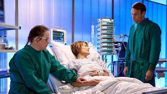 Manja sitzt am Krankenbett ihrer Mutter Veronika. Dr. Stein steht daneben.