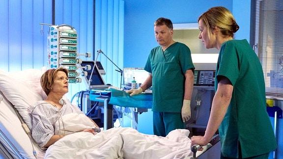 Dr. Roland Heilmann und Dr. Lea Peters am Krankenbett von Veronika.