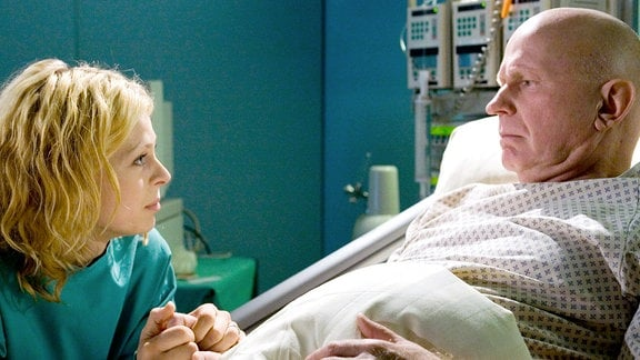 Miriana sitzt neben dem Krankenhausbett ihres Vaters und hält ihm die Hand.