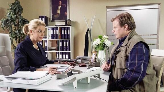 Ein Mann sitzt einer Frau an einem Schreibtisch gegenüber.