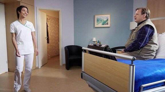 Ein Mann sitzt auf einem Krankenhausbett. Vor dem Bett steht eine junge Pflegerin.