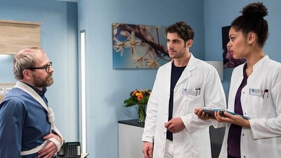 Weil Herr Kelsters Bruch operiert werden muss, bekommt er ein Bett. V.l.n.r. Theodor Kelster (Thomas Limpinsel), Dr. Niklas Ahrend (Roy Peter Link), Vivienne Kling (Jane Chirwa).