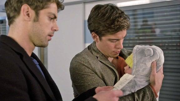 Assistenzarzt Ben Ahlbeck hat am Eingang ein Baby gefunden. Dr. Niklas Ahrend ließt den begepackten Zettel der Mutter.
