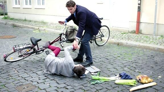Dr. Niklas Ahrend hilft einer gestürzten Radfahrerrin