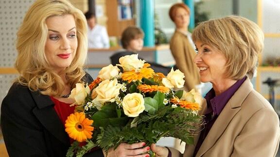 Sarah Marquardt (Alexa Maria Surholt, li.) versucht, ihren 45. Geburtstag zu verheimlichen. Tatsächlich scheint auch nur Barbara Grigoleit (Uta Schorn, re.) daran gedacht zu haben. Als sie Sarah in der Cafeteria mit einem Blumenstrauß gratuliert, versucht diese sofort abzulenken, um keine Aufmerksamkeit auf sich zu lenken.