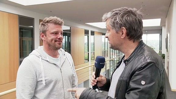 Ein Reporter spricht mit einem Mann.