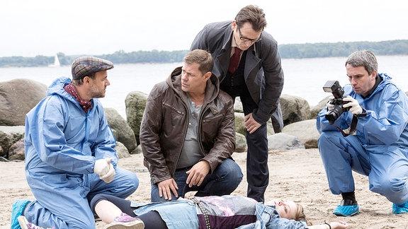 Die 19-jährige Coco (Komparsin) wird tot am Strand aufgefunden. Finn Kiesewetter (Sven Martinek, 2.v.l.), Lars Englen (Ingo Naujoks, 3.v.l.) und Dr. Strahl (Christoph Tomanek, l.) vermuten eine Methanol-Vergiftung.