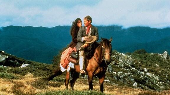 In den australischen Bergen sitzt der junge Jim Craig mit der hübschen Farmerstochter Jessica auf einem Pferd.