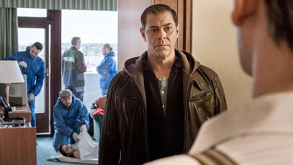 Finn Kiesewetter verhört Lars Englen in dessen Hotelzimmer.
