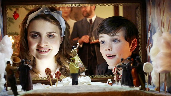 Marie Stahlbaum (Mala Emde) und Fritz Stahlbaum (Leonard Seyd) schauen erstaunt in die Zuckerwelt im Hintergrund die Eltern Frau Stahlbaum (Brigitte Hobmeier) und Vater Stahlbaum (Jürgen Tonkel)