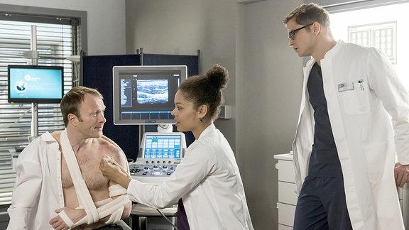 Nach dem Einrenken untersuchen die Ärzte Bernd Müllers Schulter per Ultraschall - und machen eine unschöne Entdeckung. V.l.n.r. Bernd Müller (Merten Schroedter), Vivienne Kling (Jane Chirwa), Elias Bähr (Stefan Ruppe).