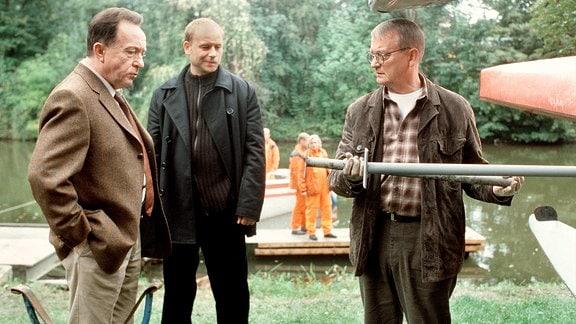 Der Kriminaltechniker Walter (Walter Nickel, rechts) zeigt den Kommissaren Ehrlicher (Peter Sodann, links) und Kain (Bernd Michael Lade, mitte) die vermutliche Tatwaffe.