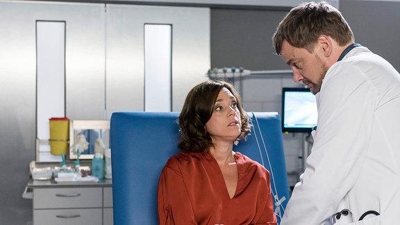 Dr. Marc Lindner (Christian Beermann, r.) informiert sich bei der Blutentnahme über Katja Beckers (Dominique Chiout, l.) Lebensumstände.