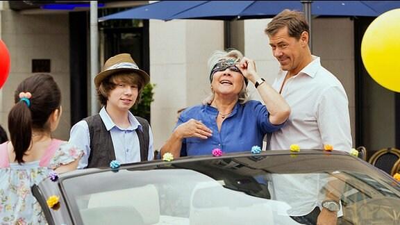 Vincent (Sven Martinek, re.), Jenny (Alea Sophia Boudodimos, li.) und Phillip (Lukas Schust) halten eine Überraschung für Rosa (Jutta Wachowiak) parat