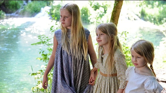 Drei Kinder an einem Fluss