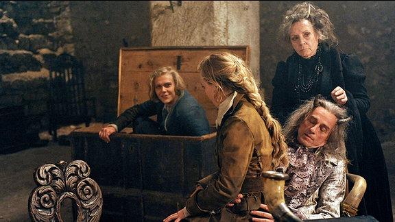 Des Teufels Großmutter (Christine Schorn, 2.v.r.) verhilft Felix (Jacub Gierszal, l.) und Prinzessin Isabell (Saskia Rosendahl, 2.v.l.) zu den drei goldenen Haaren