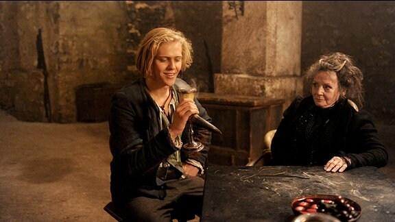 Felix (Jacub Gierszal, l.) überzeugt des Teufels Großmutter (Christine Schorn, r.) von seiner Liebe zu Prinzessin Isabell