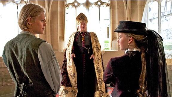Felix (Jacub Gierszal, l.) und Prinzessin Isabelle (Saskia Rosendahl, r.) sollen sich das Jawort beim Priester (Bernd Stegemann, mitte) geben.