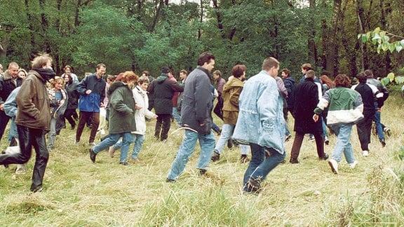 Menschen rennen durch ein Waldstück an der Grenze.